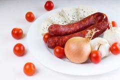 Tomates de cereza rojos alrededor de la placa blanca con las salchichas Imágenes de archivo libres de regalías
