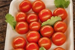 tomates de cereza rojos en una placa blanca con un fondo de madera imagen de archivo