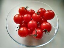 Tomates de cereza rojos en una placa transparente fotografía de archivo