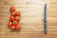 Tomates de cereza rojos maduros frescos y un cuchillo afilado que miente en una tabla de cortar de madera Concepto de la verdura  Foto de archivo