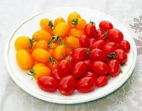 Tomates de cereza rojos y amarillos en una placa Foto de archivo libre de regalías