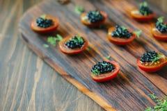 Tomates de cereza rojos y aperitivos negros del caviar en el tablero de madera Imagen de archivo