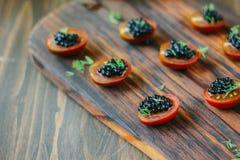 Tomates de cereza rojos y aperitivos negros del caviar en el tablero de madera Imagen de archivo libre de regalías