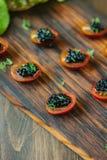 Tomates de cereza rojos y aperitivos negros del caviar en el tablero de madera Fotos de archivo libres de regalías