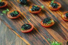Tomates de cereza rojos y aperitivos negros del caviar en el tablero de madera Foto de archivo libre de regalías