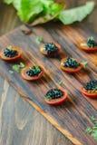 Tomates de cereza rojos y aperitivos negros del caviar en el tablero de madera Imágenes de archivo libres de regalías