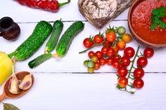 Tomates de cereza rojos y una placa de la sopa fría del gazpacho Imagen de archivo libre de regalías