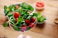 Tomates de cereza y ensalada de la albahaca en una taza de cristal en una tabla de madera fotografía de archivo
