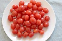 Tomates de cereza y placa de la porcelana de hueso Fotografía de archivo libre de regalías