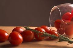 Tomates de cereza y un vidrio de vino Imagen de archivo