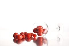 Tomates de cereza y vidrio de vino Imagenes de archivo