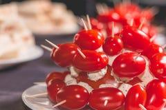 Tomates de cocktail avec du fromage sur la crête d'un plat Images stock