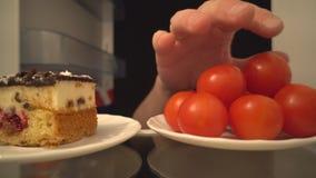 Tomates de cocktail ou gâteau délicieux Un choix difficile de nourriture saine banque de vidéos