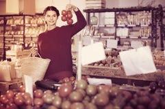 Tomates de compra de la chica joven en el mercado Foto de archivo libre de regalías