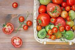 Tomates de degré différent d'une maturité sur une table dans un baske images stock