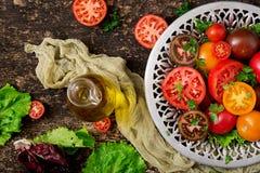 Tomates de différentes couleurs avec les herbes vertes Photo stock