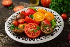 Tomates de différentes couleurs avec les herbes vertes Image stock