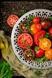 Tomates de différentes couleurs avec les herbes vertes dans une cuvette Photos libres de droits