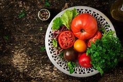 Tomates de différentes couleurs avec les herbes vertes dans une cuvette Photo stock