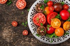 Tomates de différentes couleurs avec les herbes vertes dans une cuvette Photo libre de droits