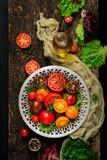 Tomates de différentes couleurs avec les herbes vertes dans une cuvette sur un fond noir Photo libre de droits