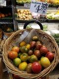 Tomates de la herencia en cesta redonda en venta en el mercado imagenes de archivo