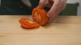 Tomates de la rebanada por la mitad clip el cocinar, comida y concepto casero - cercanos para arriba de la pimienta masculina del almacen de video