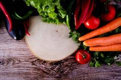Tomates de madera del piso, perejil, berenjena, pimienta roja, pimienta verde Foto de archivo