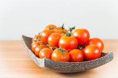 Tomates de plat en bois Photos stock