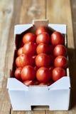 Tomates de prune mûres dans une boîte en carton du marché photographie stock libre de droits