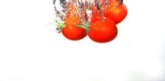 Tomates de raisin dans l'eau photos stock