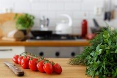 Tomates de raisin sur la vigne sur le compteur en bois à côté d'un couteau de cuisine a Images stock