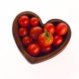 Tomates de rouge d'amour ! Dans la cuvette de forme de coeur - d'isolement sur le blanc Photos libres de droits