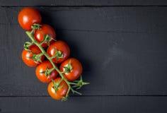 Tomates de vigne sur la photo de table en bois noire rustique de vue Photographie stock libre de droits