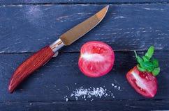 Tomates del corte con una navaja imagenes de archivo