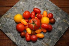 Tomates del relevo en pizarra Imagenes de archivo