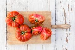 Tomates deliciosos crus na placa de corte na tabela de madeira velha dentro foto de stock