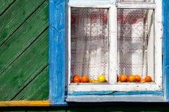 Tomates derrière la maison de village de fenêtre Image libre de droits