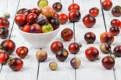 Tomates diferentes na bacia no fundo de madeira branco Imagens de Stock