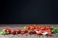 Tomates dispersados en la tabla de madera Fotos de archivo