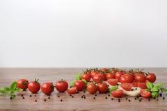 Tomates dispersados en la tabla de madera Imagen de archivo