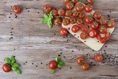 Tomates dispersados en la tabla de madera Imagenes de archivo