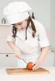 Tomates do rezhit do cozinheiro chefe da menina Imagem de Stock Royalty Free
