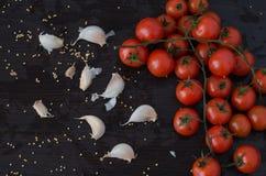 Tomates e alho de cereja, no fundo preto Imagem de Stock