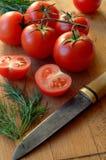 Tomates e aneto com a faca na placa de corte Fotos de Stock Royalty Free
