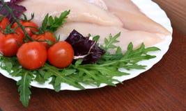 Tomates e carne crua da galinha com ruccola foto de stock