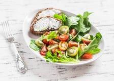 Tomates e ervas salada do jardim e sanduíche frescos do queijo em uma placa cerâmica branca em um fundo de madeira claro Fotografia de Stock