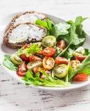 Tomates e ervas salada do jardim e sanduíche frescos do queijo em uma placa cerâmica branca em um fundo de madeira claro Foto de Stock