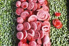 Tomates e ervilhas verdes vermelhos congelados Fotografia de Stock Royalty Free