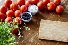 Tomates e especiarias da placa de corte Imagens de Stock Royalty Free